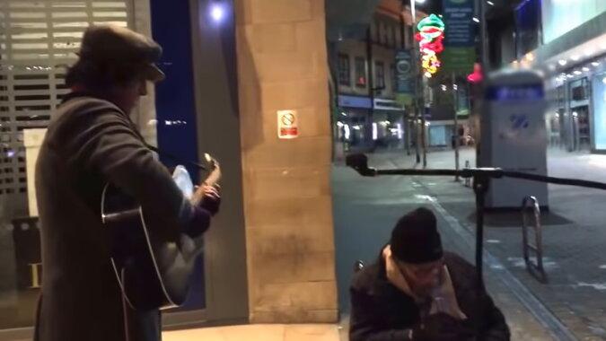 Ein Odachloser und ein Straßenmusiker. Quelle: Screenshot YouTube