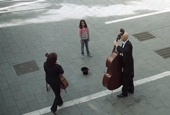 Das Mädchen gab Straßenmusikanten ein paar Münzen und das Konzert begann