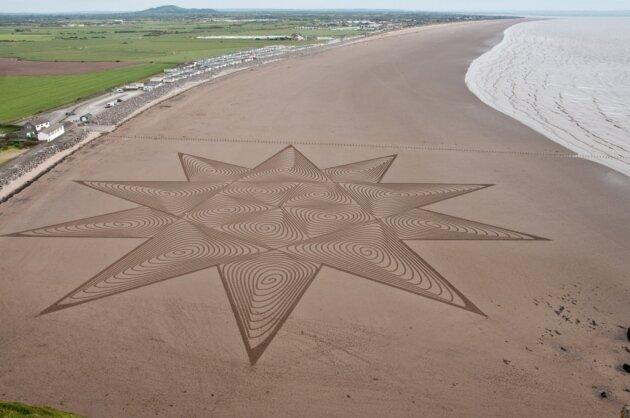 Großflächiger Ansatz: Der Künstler kreiert wunderschöne Designs aus Sand an den Stränden