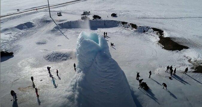 Wie ein Eisvulkan aussieht, der über dem Wasser erschienen hat und dessen ausgestoßenes Wasser sofort friert